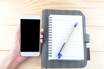 smartphone in hand with notebook paper organizer pen on wooden desk