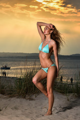 Sexy bikini model with beautiful body on a beach. Attractive young woman in a blue bathing suit relaxing on the beach. Sunset time.
