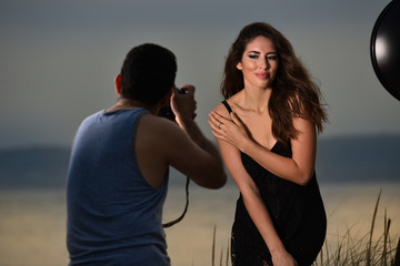 Photographer shooting beautiful brunette model at the beach during sunset time.