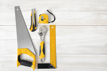 Building tools including centimeter ruler, wrench and cutter placed in the left side on wooden surface with open space