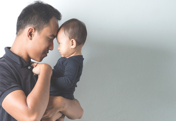 Young Asian father holding his adorable baby