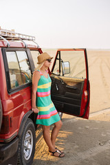 Shot of young female traveler in hat and sunglasses standing near car on the beach