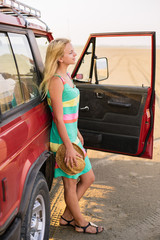 Young woman traveler standing near the car on the beach.