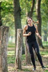Athletic woman exercising outdoors, running in between wooden stumps