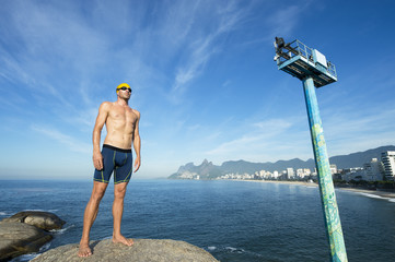 Athlete swimmer with swimming cap standing in front of the Rio de Janeiro skyline at Arpoador, Ipanema Beach