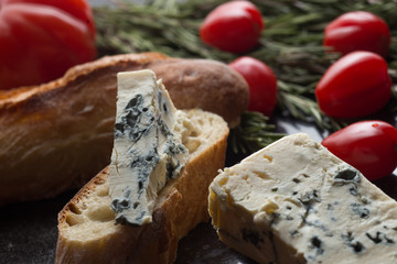 Blue cheese with french baguette, tomato and herbs on black marble table. Traditional snacks in France and Italy.