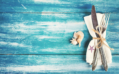 Table setting with a seaside theme. fork and knife, napkin, shells.