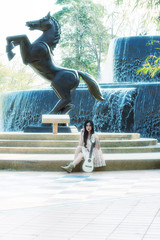 girl playing guitar with statue of a horse near the fountain in park