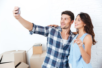 Young couple making selfie holding keys in new flat