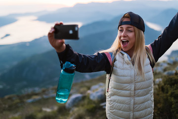 Young traveler taking a selfie picture on top of a mountain