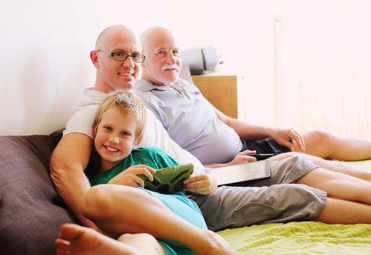 father, grandfather and son playing games on tablets and reading