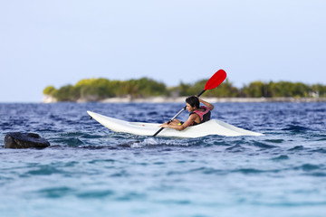 asian young boy rowing in sea kayak