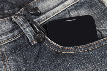 earphones with mobile smartphone in the pocket old jeans