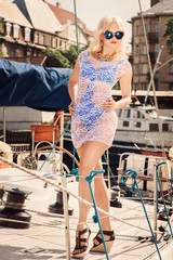 Young beautiful blond woman in white transparent dress and swimsuit standing on yacht at sunny day