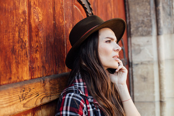 young woman with a hat next to an old wooden door talking at cel