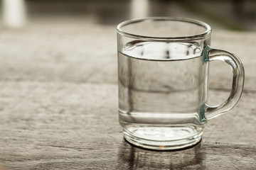 Glass of water on a wooden floor in the coffee shop with the mor