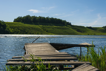 old wooden jetty at spring lake on blue sky background