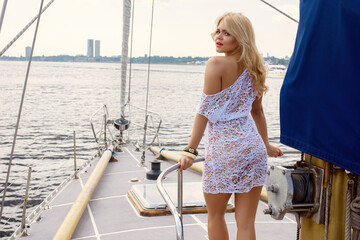 Young beautiful blond woman in white transparent dress standing on yacht at sunny day