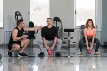 Group Of People Exercise With Kettle Bell