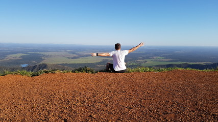 Homem sentado no topo da montanha e admirando a paisagem