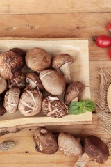 Shiitake mushrooms for cooking on wood background.