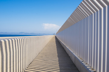 Spain, Andalusia, Tarifa, Light and shadows created by a fence on a concrete surface