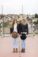 Two women standing on sports field