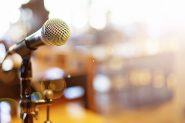 Microphone over the Abstract blurred photo of conference hall or