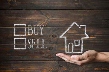 buy or sell house written on wooden boards. Drawing with chalk a