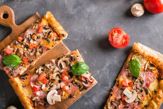 a slice of square pizza with basil tomatoes and mushrooms on a wooden board. Top view. Copyspace. Pizza on the gray table
