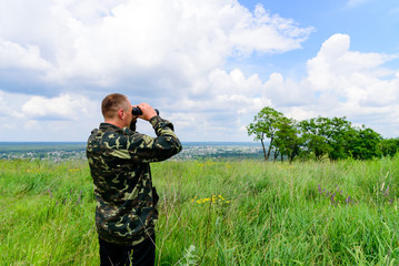 Adult man looks in the binocular at the nature skyline