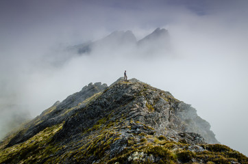 Person on top of misty rocky mountain