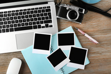 Laptop, photos and camera on a wooden desk background, top view