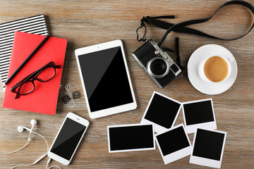 Tablet, phone, photos and cup of coffee on a wooden desk background, top view