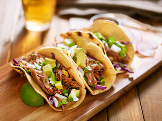 Sticker - three  pork carnitas street tacos in yellow corn tortilla with avocado, onion, cilantro and cabbage