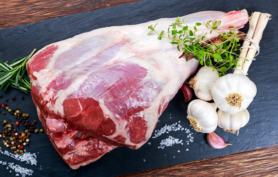 Raw lamb leg on blue stone background with herbs