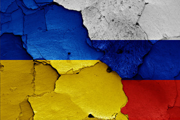 flags of Ukraine and Russia painted on cracked wall