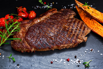 Grilled Beef Sirloin Steak on blue stone background, with vegetables.