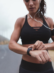 Fitness woman adjusting smart watch while exercising outdoors