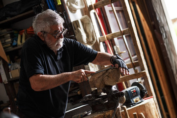 Senior sculptor working on his sculpture in his workshop.
