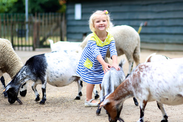 Toddler girl petting little goats in the kids farm. Cute kind child playing and feeding animals in the zoo.