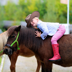 Lovely cowgirl sits on little pony horse in the farm. Pretty preschooler girl wearing cowboy hat playing with animals outdoors on sunny day.