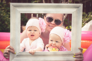 Family portrait with mother and her baby girl twins during outdoor party