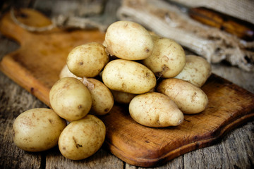 Raw potato food. Fresh young potatoes in old rustic wooden background