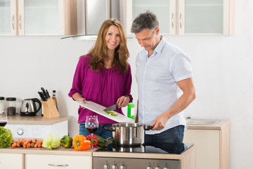 Couple Preparing Food In Kitchen