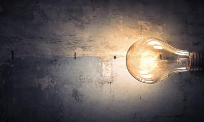 Light bulb on stone surface