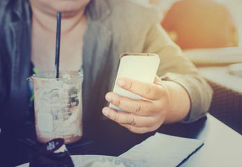 Business woman holding smartphone in coffee shop.