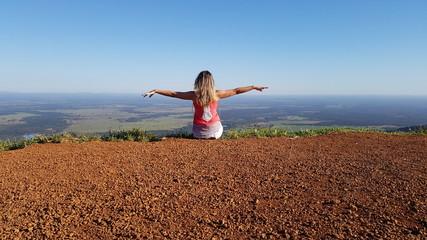 Mulher sentada no topo da montanha e admirando a paisagem