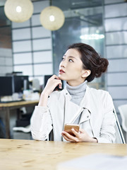 contemplating asian business woman sitting in office