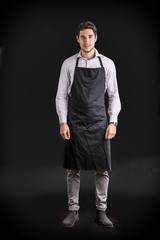 Young chef or waiter wearing black apron